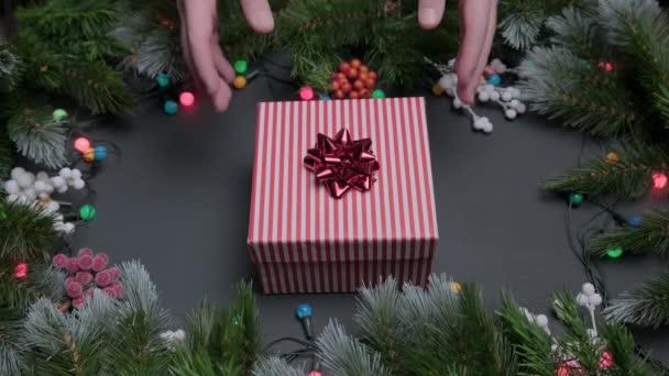 Mužské ruce dát požadovaný dárek na stůl a vzít ho zpět, dárková krabice s červenou mašlí na vánočním pozadí, zdobené jedlovými větvemi a pestrobarevné věnce světel. Dárek na Nový rok a Vánoce.