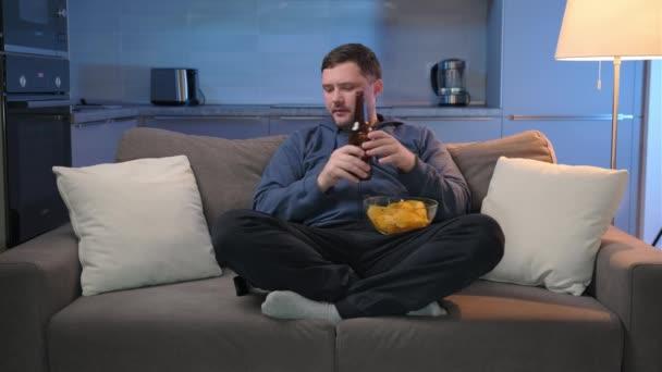 A férfi otthon este TV-t néz, és TV-csatornákat vált távirányítóval, hogy szórakoztató műsort keressen, alkoholt és chipset iszik. Egyedül lenni esténként..