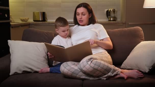 Die fürsorgliche Schwangere liest ihrem geliebten blonden Kind ein Buch vor, während sie abends auf dem Sofa im Wohnzimmer sitzt. Eltern bringen Kind Lesen vor der Schule bei, Fernunterricht, Konzeptkindentwicklung.