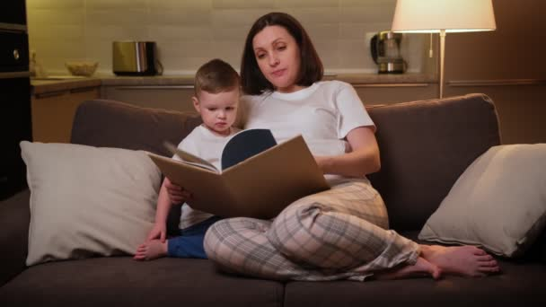Rodič učí dítě číst před školou, distanční vzdělávání, koncepce vývoje dítěte. Pečující těhotná matka čte knihu pro své milované blond dítě, zatímco sedí na pohovce v obývacím pokoji ve večerních hodinách.