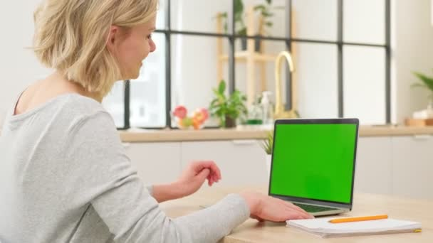 Female student convenes a conference on a laptop with blank green screen of distance learning at home. Student girl is chatting on a webcam while preparing for a test or exam with an online teacher.