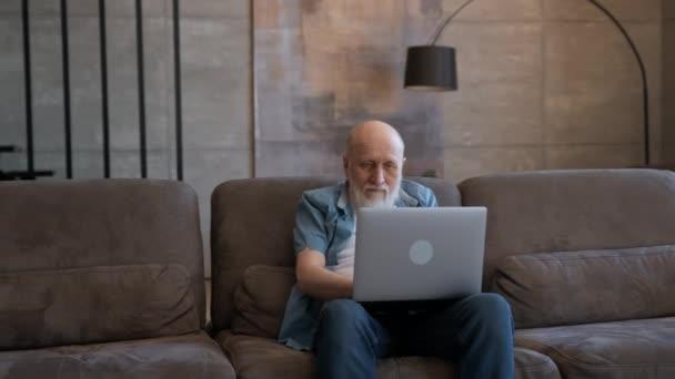 Alter Opa, glücklich, die Hände in die Höhe gereckt, auf den Laptop-Bildschirm starrend, auf dem Sofa sitzend. Emotionen des Gewinnens im Rentner, des Gewinnens im Casino, des Gewinnens bei Sportwetten, des Gewinnens im Videospiel.