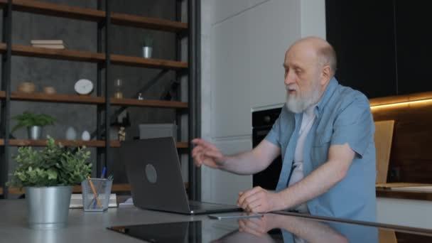Der alte Großvater kommuniziert per Webcam mit seiner einheimischen liebenden Familie, gestikuliert und winkt mit den Händen. Kommunikation über Videokonferenzen, Online-Schulungen, Fernstudium, berufliche Entwicklung.