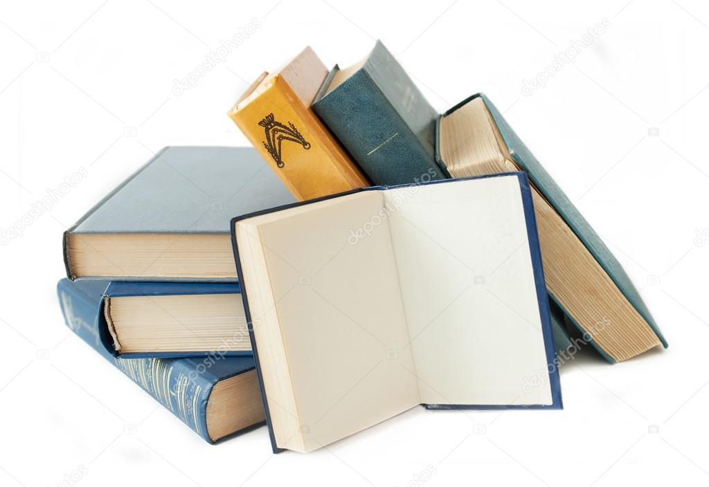 la pila de viejos libros de color en la mesa y uno abierto sobre un ...