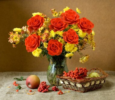 Still life with huge bunch of autumn flowers and red roses, apples and rowan berries
