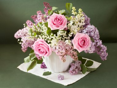 Artistic still life with huge bouquet of lilac and lily of valley flowers and roses on painting background