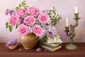 schönes Stillleben mit lila und rosa Rosen Blumenstrauß, Bücherstapel und aufgeschlagenes Buch auf Malgrund