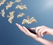 Fotografia Mano che tiene telefono mobile moderno e libri di volare via. Concetto di formazione