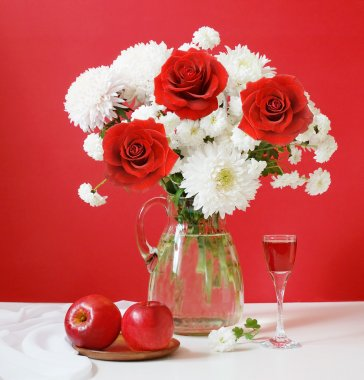 Still life with huge bunch of white flowers and red roses, apples and wine on artistic background
