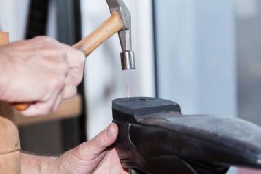 Shoemaker repairs a shoe