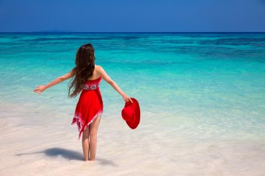 Happy woman enjoying on exotic beach in summer by tropical blue