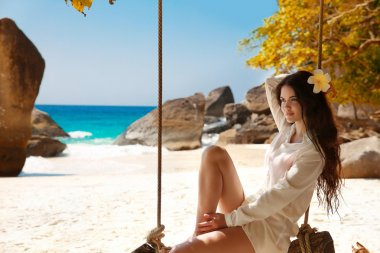 Attractive smiling brunette summer portrait on exotic vacation.