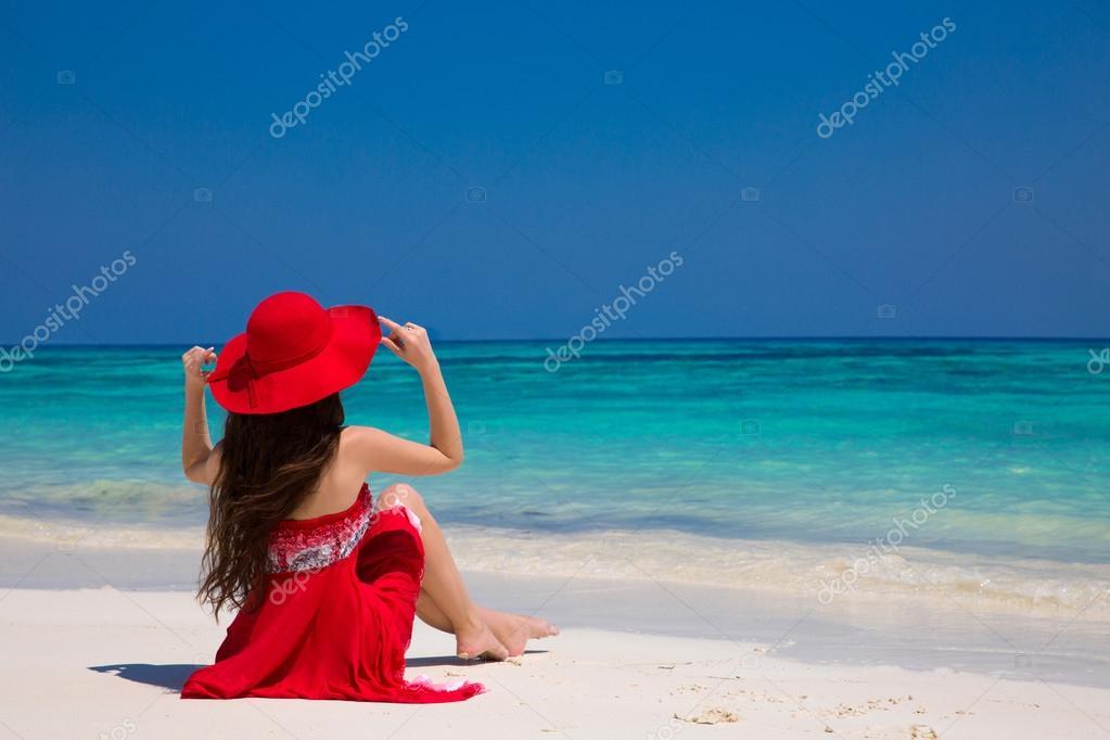 Happy woman enjoying beach relaxing joyful on white sand in summ