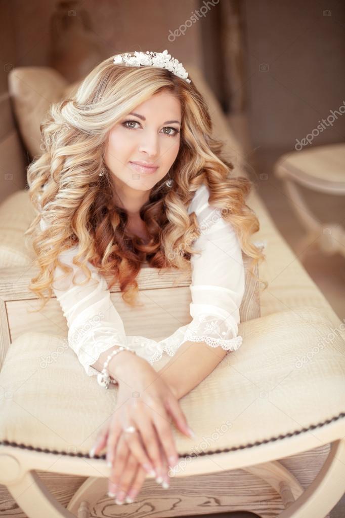 0889a8cc583767 Макіяж. Весільна зачіска. Красиві нареченої. Привабливий блондинка дівчина  з давно кучерявого волосся, лежачи на сучасний диван в інтер'єр квартир —  Фото ...