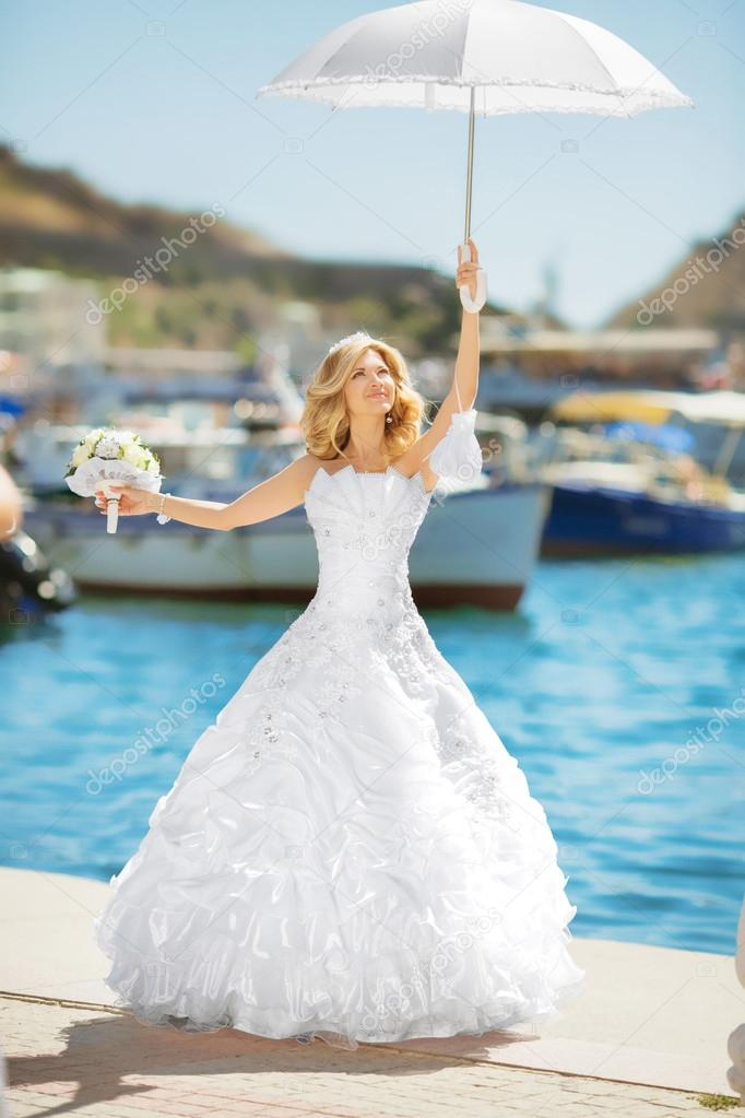 Beautiful bride in wedding dress with white umbrella posing over ...
