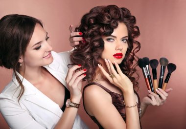 Curly hair. Beauty makeup. Professional artist woman applying ma