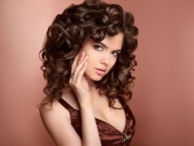 Hairstyle. Beautiful young woman with long curly hair, beauty ma
