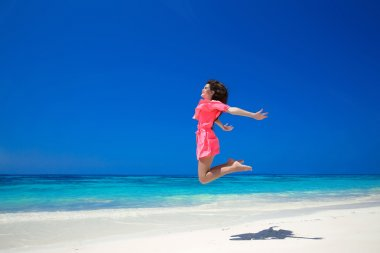 Enjoyment. Happy free woman jumping over sea and blue sky, brune