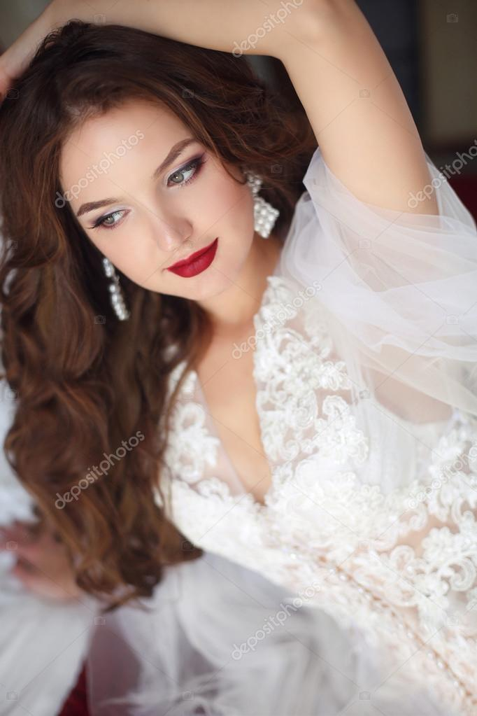 0cedd89ae03 Belle femme souriante de la mariée. Maquillage de mariage. Modèle jolie  jeune fille avec des cheveux long ondulés porter en robe blanche sexy  boudoir