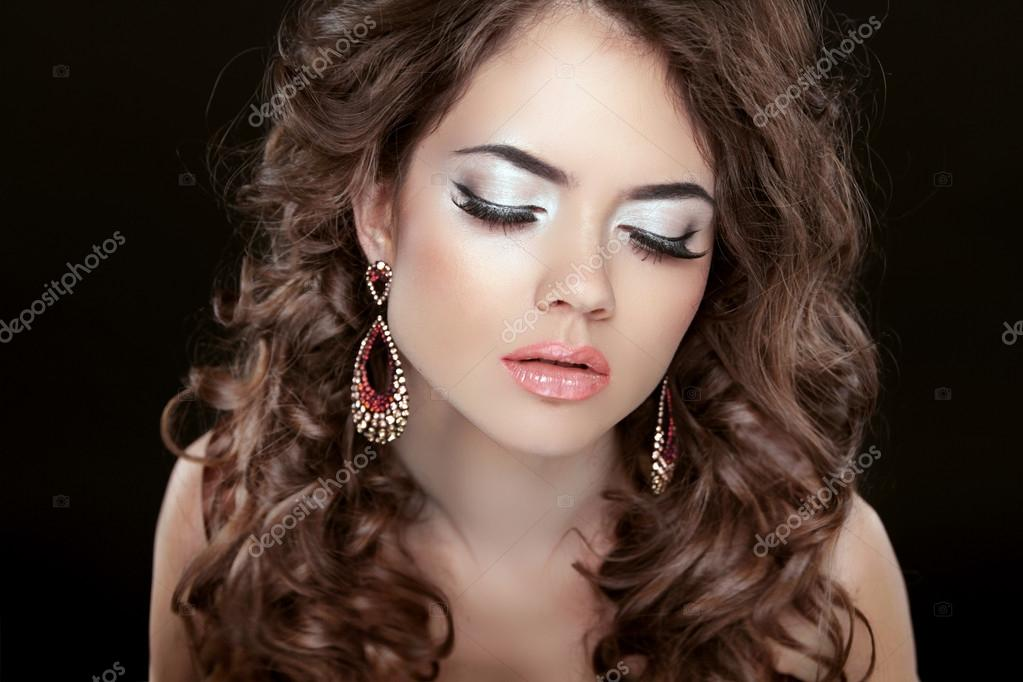 Beautiful fashion woman with makeup, long wavy hair and earrings