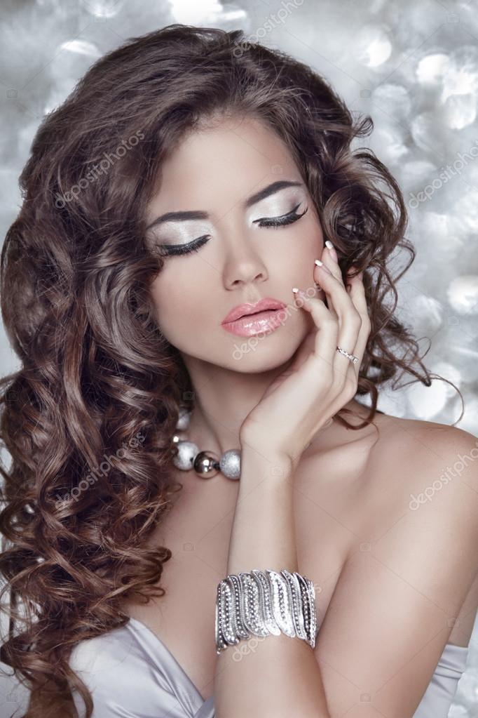 Long wavy hair. Beautiful brunette woman with sensual lips, make