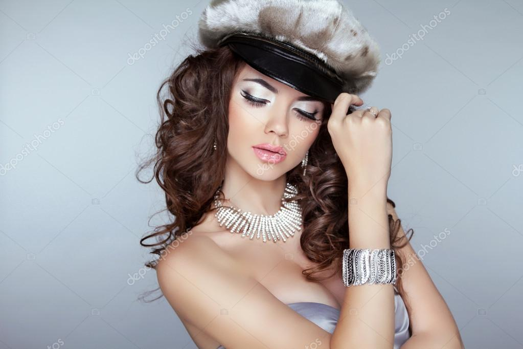 Beautiful woman model with makeup, curly hair and fashion jewelr