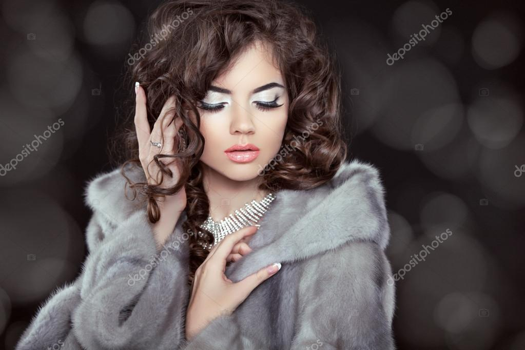 Beautiful fashion brunette woman model in mink fur coat isolated