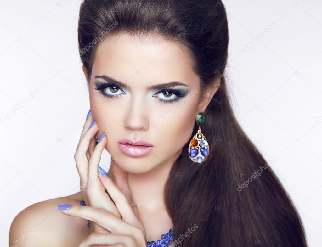 Beautiful Brunette young woman with fashion earring. Makeup. Man