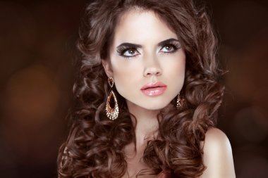 Beautiful girl model with curly long hair and fashion earrings