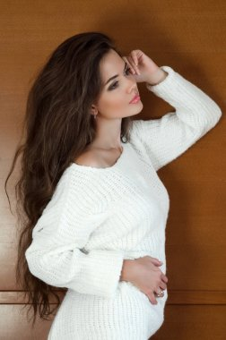 Beautiful brunette woman in white sweater with Healthy Long Wavy
