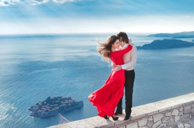 Young married couple embracing. Fashion girl in red dress with h