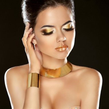 Fashion Beauty Girl Isolated on Black Background. Golden Jewelry
