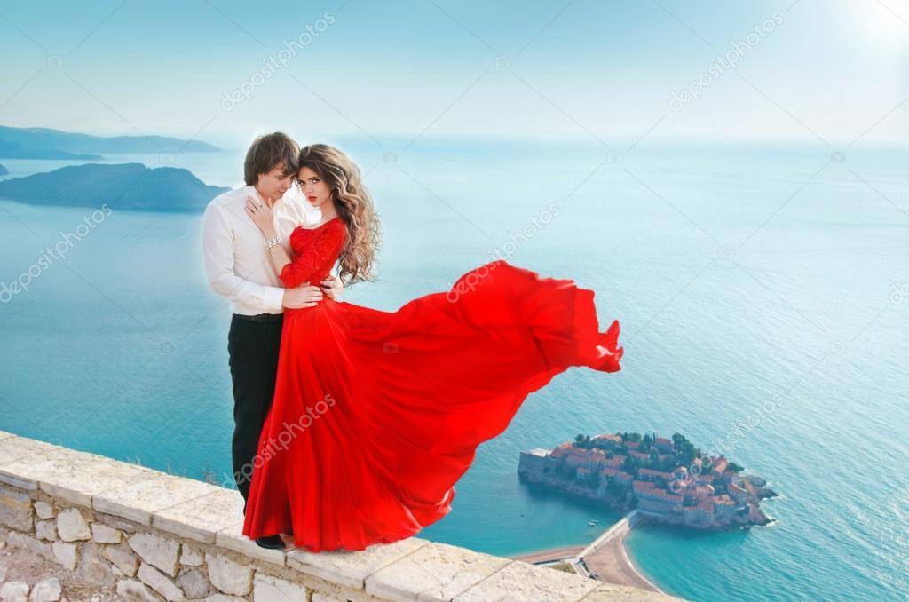 Romantic young couple in love over sea shore background. Fashion
