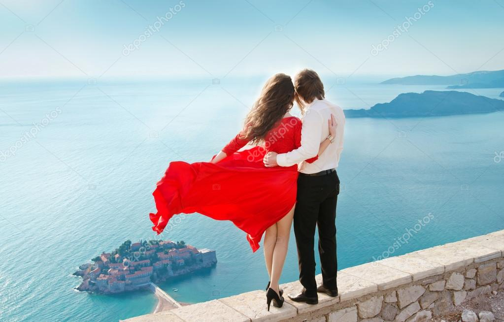 Romantic young couple in love over sea shore background. Fashion