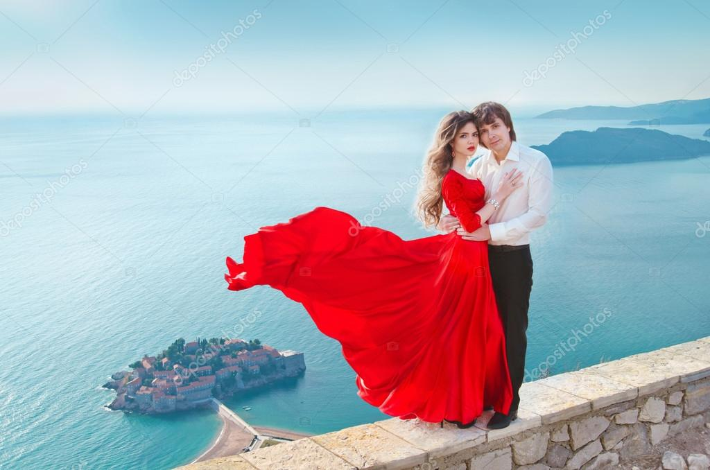 Romantic young couple in love over blue sea shore background. Fa