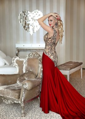 Fashion beautiful blond Girl model with elegant hairstyle in red