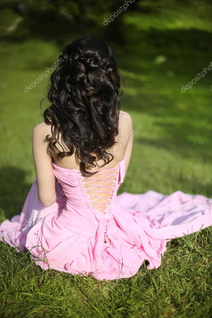 Brunette bride resting and sitting on green grass at spring park