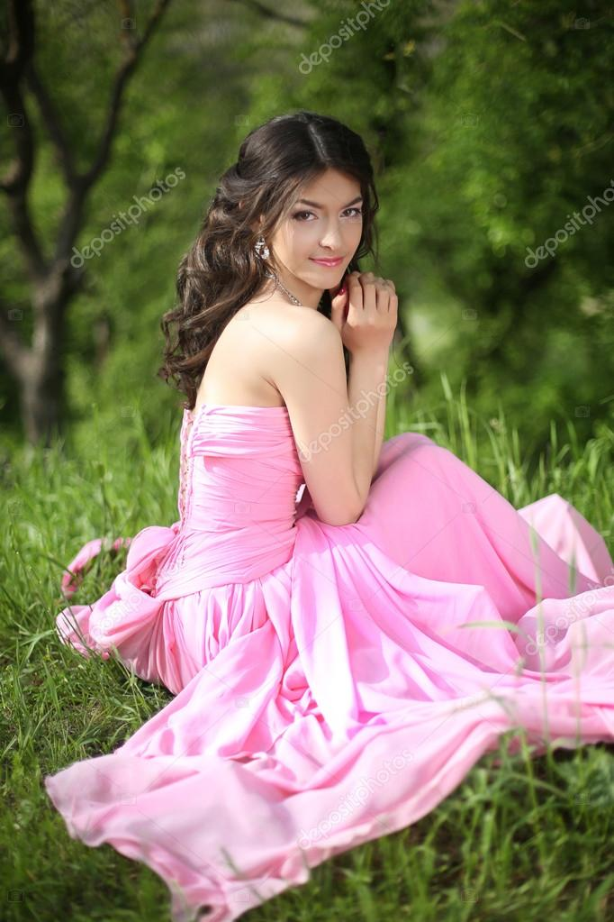 Smiling young brunette girl resting and sitting on green grass a