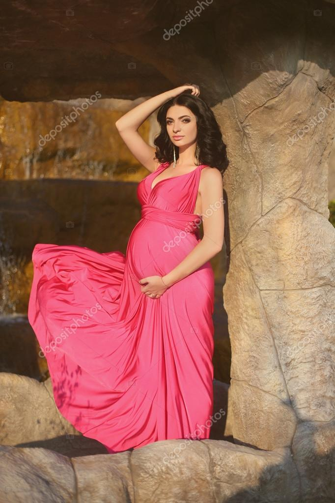 83022fd384828 Beautiful pregnant woman wearing in blowing pink dress posing ag– stock  image
