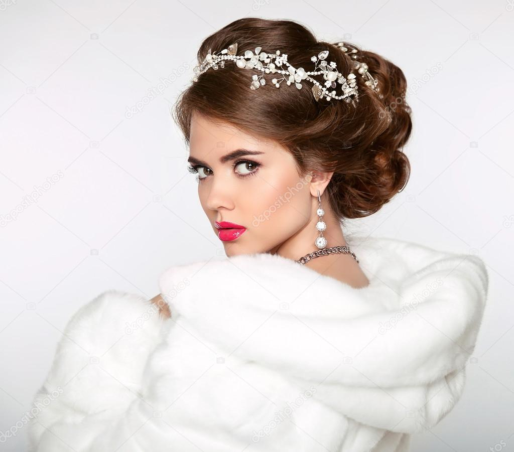 Elegant woman in white fur coat. Wedding Hairstyle. Beautiful fa ...