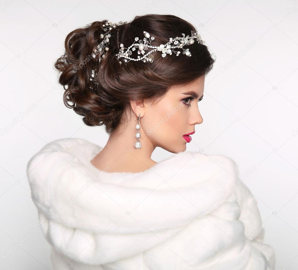 Elegant brunette woman in white fur coat. Wedding Hairstyle. Bea ...