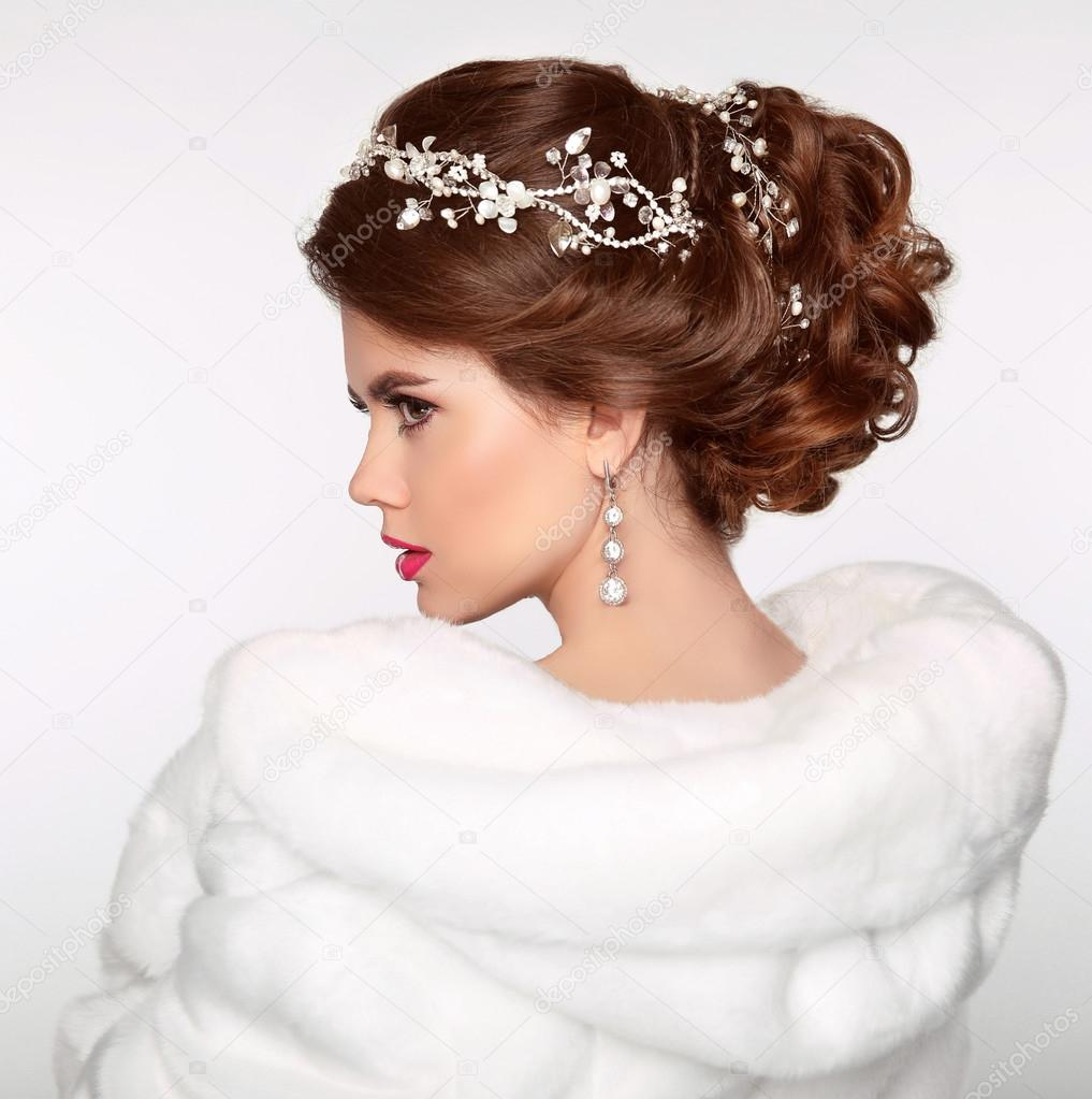 Wedding Hairstyle. Attractive girl in white fur coat. Jewelry Ea ...