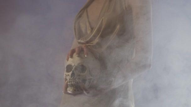 Frau in Partykleid und Maske mit Totenkopf im Rauch. Pandemiekonzept. Vertikales Schwenken