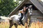 Fotografia Ritratto di bella donna sul cavallo vicino al granaio