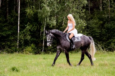 Beautiful blonde woman and gray horse riding