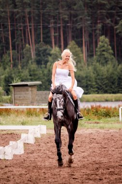 Beautiful bride riding gray horse in summer