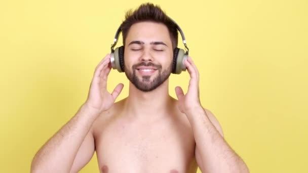 Hezký mladý muž poslech hudby na barevném pozadí
