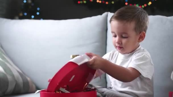 Little baby boy opening Christmas gift at home