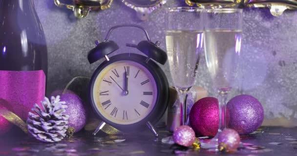 Ébresztőóra, újévi dekoráció és pezsgő az asztalon