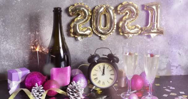 Ébresztőóra, újévi dekoráció, pezsgő és pezsgő az asztalon